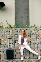 Happy young female traveler sitting on the brick wall. Next to her luggage.
