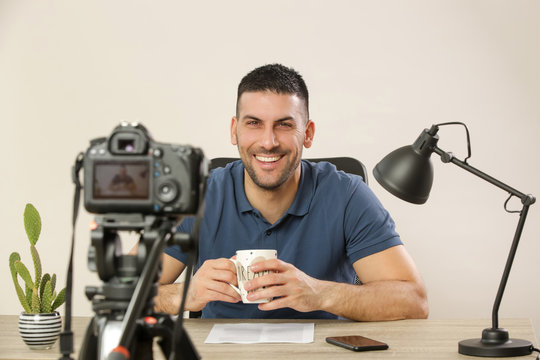 Young smiling cheerful man sitting at the office desk in front of the camera making a video. Male blogger recording a video tutorial.