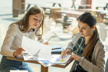 two beautiful business girls in a cafe working with documents