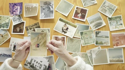Wall Mural - Top view of a senior caucasian woman looking at old photos themes of memories nostalgia photos retired