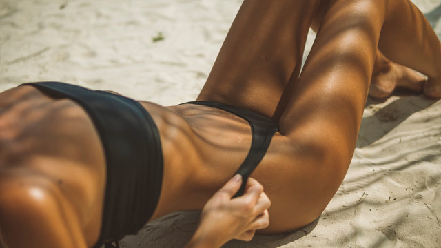 long-legged model in black bikini is on the ocean beach lying in a sexy pose,