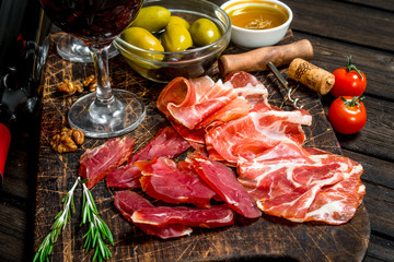 Antipasto background. Different meat snacks with red wine.