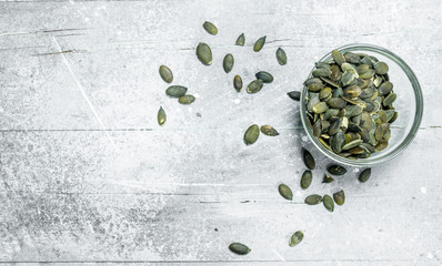 Pumpkin seeds in a glass bowl.