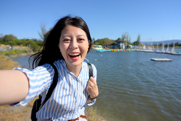 Cheerful young woman tourist having fun taking smartphone selfie pictures of herself beside the lake. Happy Asian girl model taking self portrait smiling happy by port in summer lifestyle.