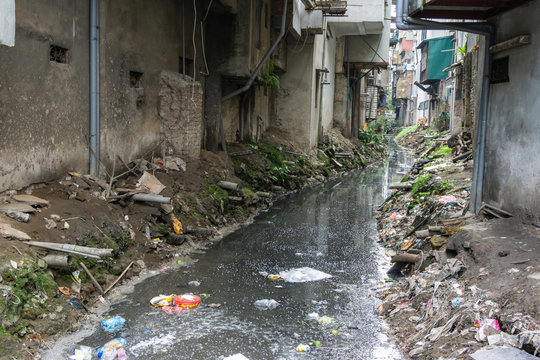 Dirty polluted waste water in big city with garbages. Environment pollution. Urban environment issues in developing countries