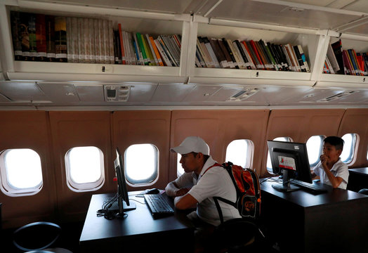 A man and a child look at computers inside an old McDonnell Douglas DC 9-14 airplane that houses a virtual library in Mexico City