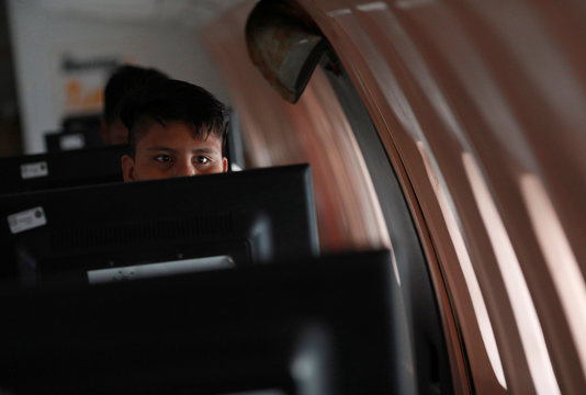 A man uses a computer inside an old McDonnell Douglas DC 9-14 airplane that houses a virtual library in Mexico City