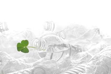 白い背景に積み重なった沢山のペットボトルと緑の葉