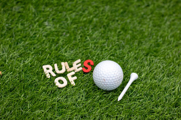 Rules of golf with golf ball and tee on green grass