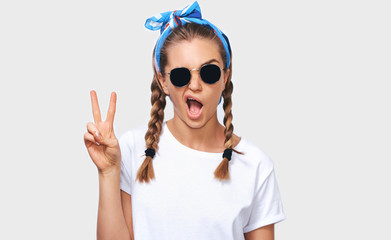 Horizontal studio portrait of cheerful blonde young woman wearing trendy sunglasses, white t-shirt and blue headband, showing peace sign. Student girl going funny with braids hairstyle. People emotion