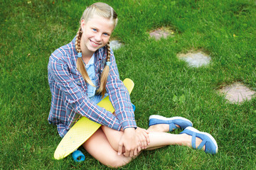 Нappy, laughing child wearing cool fashion clothing posing with colorful skateboard against green grass, urban style.