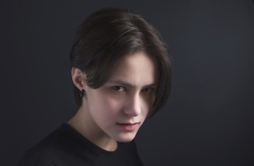 Portrait of an impulsive beautiful young girl with short hair in a black t-shirt and top