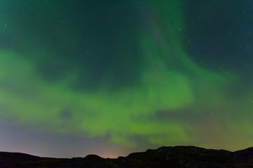 Green northern lights over the hills, aurora.