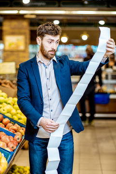 Portrait of an elegant man with shocked emotions holding very long shopping list while buying food in the supermarket