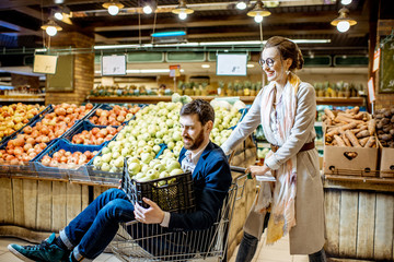 Happy couple having fun while riding in the shopping cart in the supermarket buying fresh fruits