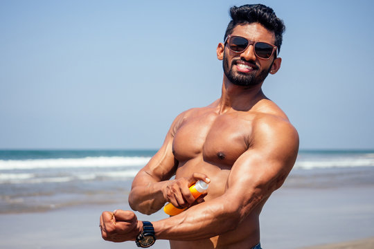 happy young african man on the beach.Handsome and confident Masculine hard fitness bodybuilder with sixpack.India model male perfect abs, shoulders,biceps, triceps,chest holding a bottle of sunscreen