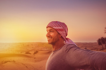 man with outstretched arms in the desert while sunset