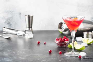 Classic alcoholic cocktail cosmopolitan with vodka, liqueur, cranberry juice, lime, ice and orange zest, gray bar counter background, bartender tols, space for text