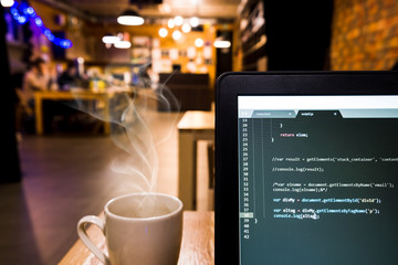 Laptop with programming code in office desk. Low depth of field.