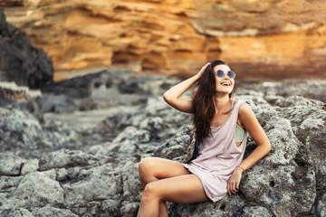 Fotobehang Pretty long hair brunette tourist girl relaxing on the stones near sea.