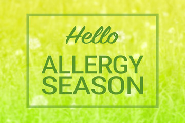 Natural green grass and flowers background and hello allergy season text sign. Spring summer seasonal allergies concept.
