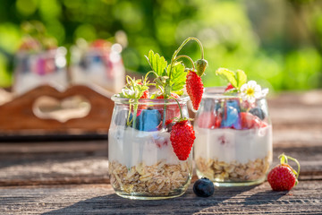 Healthy granola in jar with yoghurt and berries