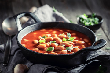 Hot baked beans with tomato sauce and fresh herbs