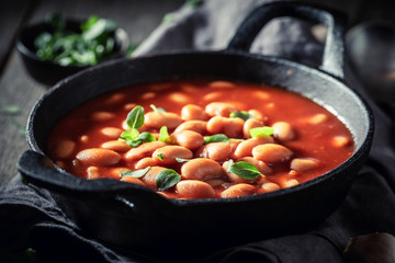 Spicy baked beans with tomato sauce and fresh herbs