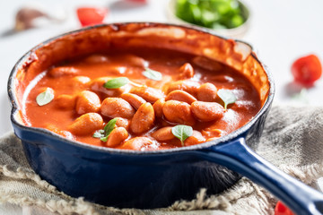 Hot baked beans with garlic and fresh tomatoes