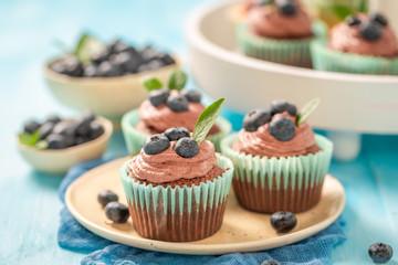 Fresh cupcake with blueberries and chocolate cream