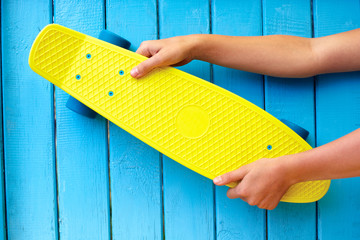 Yellow skateboard in human hands on azure wooden background. Concept trend and youth hobbies