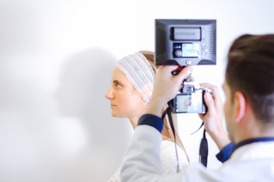 Doctor taking picture of young female patient before aesthetic treatment on white background.