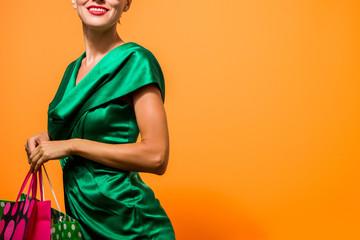 Beautiful caucasian woman in green dress shopping holding shopping bag