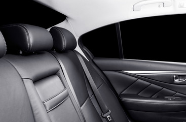 Back passenger seats in modern luxury car. Frontal view. Black perforated leather with white stitching. Car detailing. Leather comfortable black seats. Car interior details. Car inside