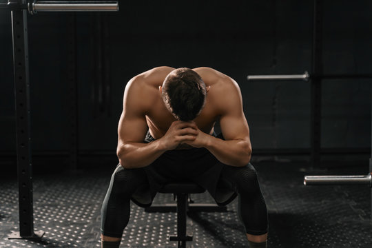 Strong sporty man sitting on gym bench suffering breakdown to overcome