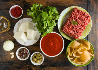 Ingredients for pasta shells cooking, minced neat, onion, garlic, tomatoes, green olives, parmesan cheese. Wooden rustic table, top view