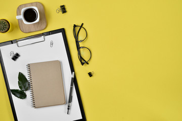 Office desk workspace with blank clip board, office supplies, pen, cactus, green leaf, coffee cup on a wooden stand and eye glasses on yellow background. Flat lay, top view blog concept