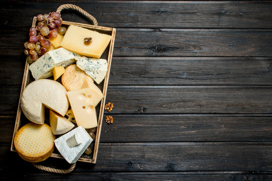 Different types of cheese in a wooden tray with grapes .