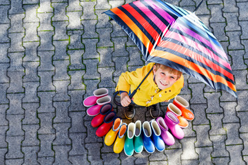 Little kid boy and group of colorful rain boots. Blond child standing under umbrella.