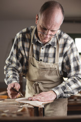 Erfahrener Instrumentenbauer fährt mit der Hand über ein Werkstück