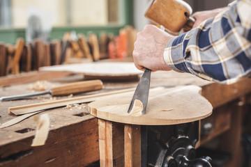Hände eines Instrumentenbauers arbeiten mit Klüpfel und Beitel