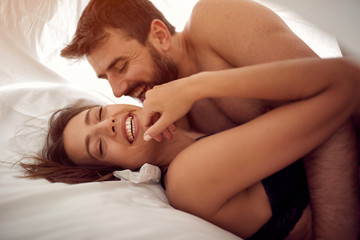 Smiling young couple lying and hugging in bed .