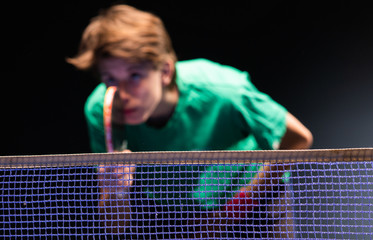 Young boy playing ping pong table tennis