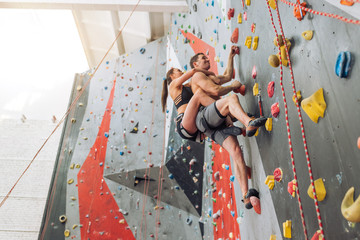 young fit man and woman have joined a climbing gym. low view. full length photo. speed freestyle