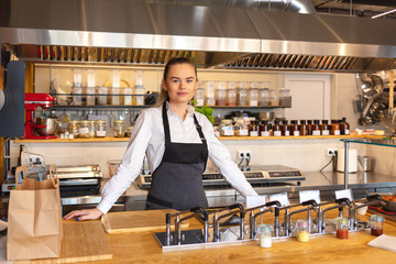 Portrait of young woman standing behind kitchen counter in small eatery – restaurant owner wearing apron looking confident at camera smiling
