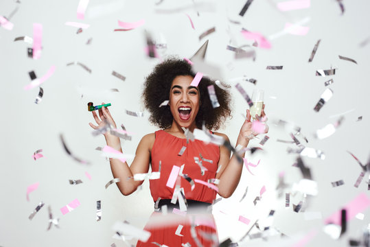 Portrait of a happy afro american woman in party hat holding glass of champagne and party whistle, while standing with opened mouth under confetti rain