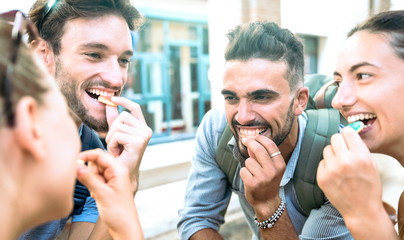 Happy millenial friends having fun at city center eating sugar candies - Z generation friendship concept with young millenial people hanging out together - Guys and girls on youth lifestyle mood Fototapete