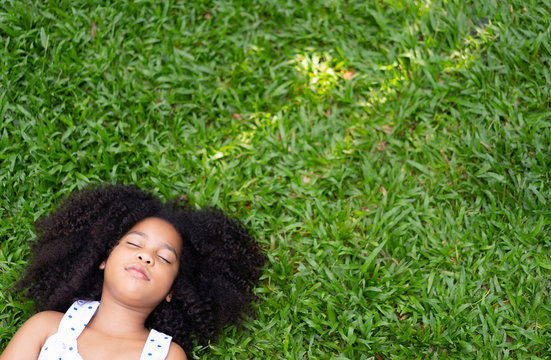 Top view of Child or little girl relax or sleeping or lying on grass on the grass in summer,rest one's eyes or During the lunch break with copy space for text your. freedom ,peace lifestyle concept