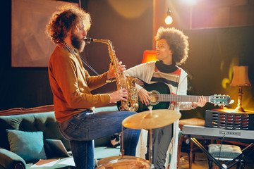 Mixed race woman playing acoustic guitar while man playing saxophone. Home studio interior.