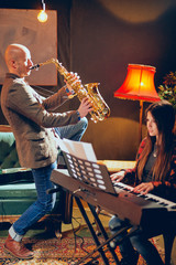 Bald Caucasian man playing saxophone in home studio while young talented woman playing clavier.